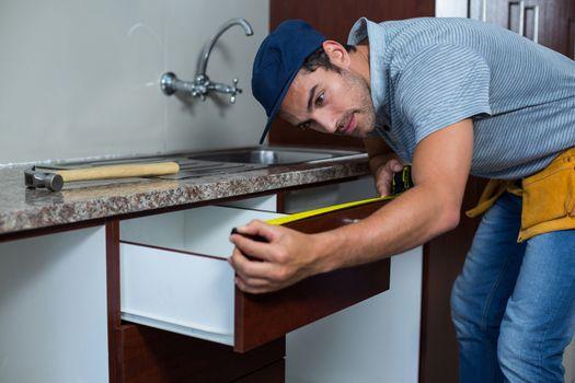 Man measuring drawer size