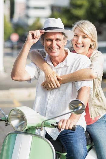 Smiling couple sitting motor scooter