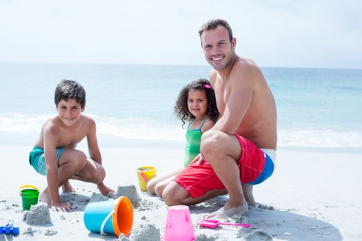 Smiling father playing with daughter and son on sea shore at beach