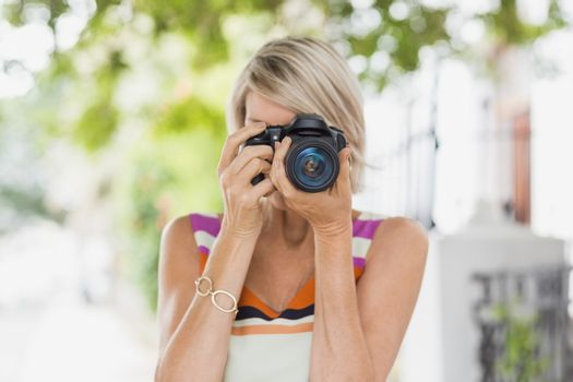 Woman taking photograph from camera