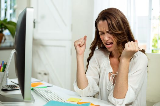 Irritated businesswoman at desk in office