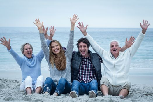 Portrait of cheerful family with arms raised sitting at sea shore
