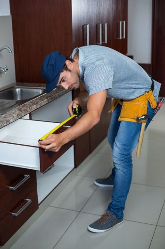 Full length of man measuring drawer size
