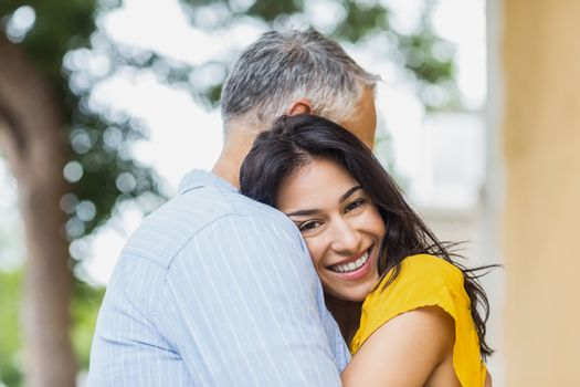 Portrait of cheerful woman hugging man outdoors