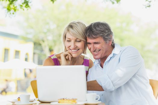 Couple using laptop sitting at cafe