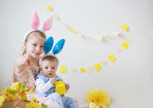 Two cute little children boy and girl wearing bunny ears in Easter decor