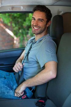 Handsome driver fastening car seat belt