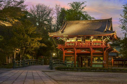 "Bridge named bridge of the gods ""神橋"" (shinbashi) and central gate named the cherry door ""桜門"" (sakuramon) of the Shintoist Nezu shrine of the 18th century in Tokyo at sunset."