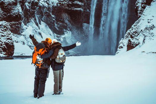 Happy couple enjoying amazing view on Skogafoss waterfall, having fun in winter travel to Iceland, active wintertime honeymoon