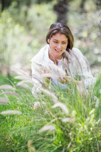 Young woman looking down on grassy field