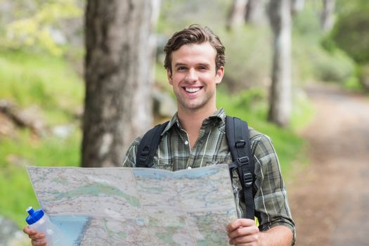Happy young man with map on footpath
