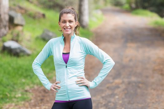 Portrait of female jogger standing on footpath