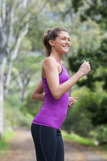 Happy young woman running on footpath