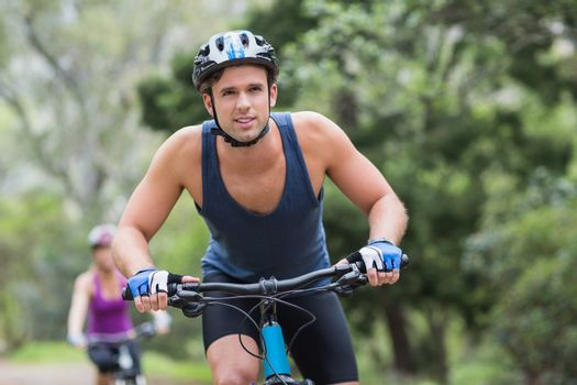 Man riding cycling on footpath in forest