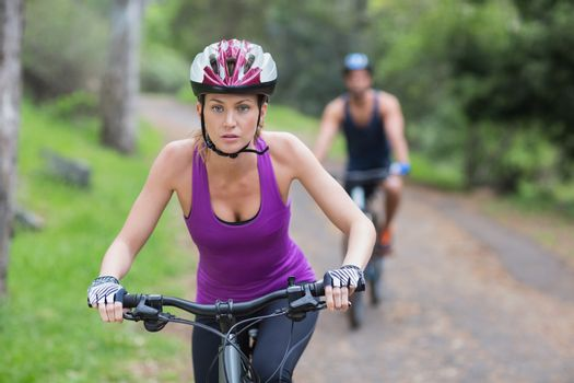 Young woman riding bike on footpath