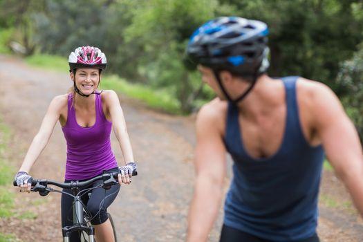 Female biker looking at man on footpath