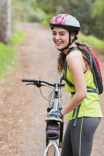 Cheerful woman with bike standing on footpath