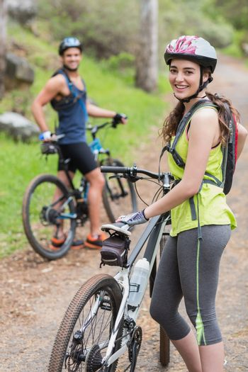 Young happy biker with man on footpath