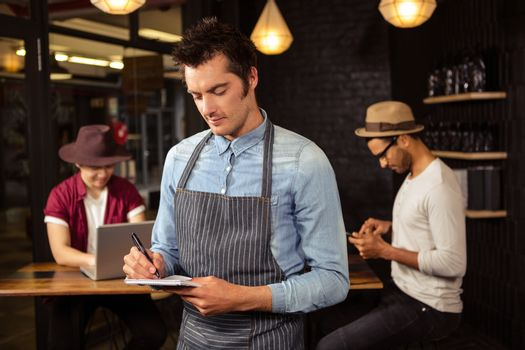 Waiter writing order on his notebook