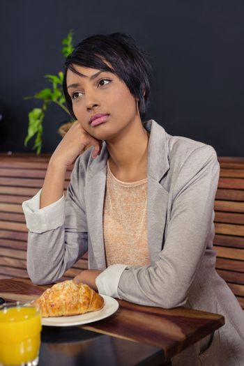 Unhappy woman sitting with breakfast
