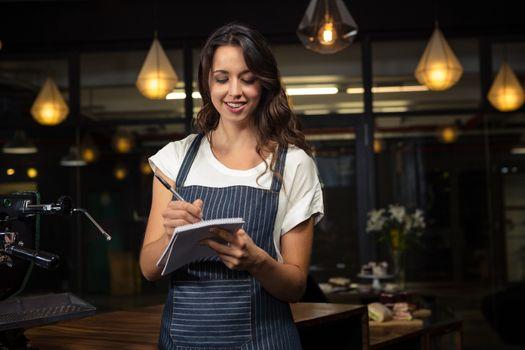Pretty barista taking notes
