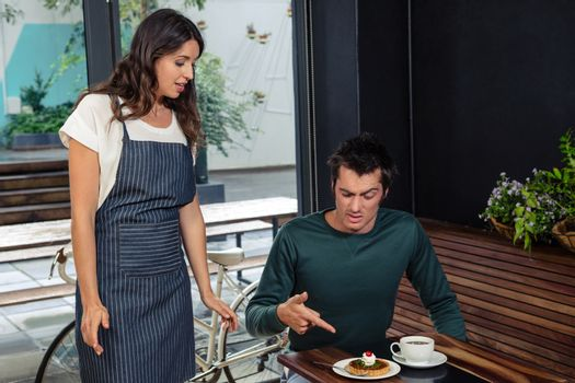 Angry client quarreling with waitress about wrong order