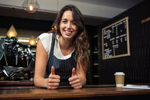 Portrait of smiling barista with thumbs up