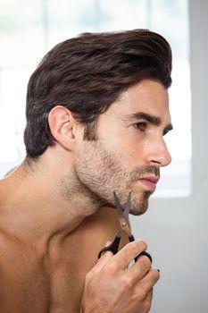 Young man cutting beard