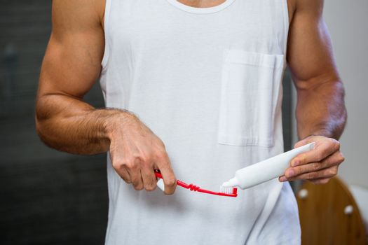 Close-up of man squeezing toothpaste on toothbrush
