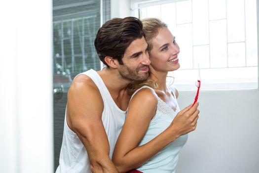 Happy couple hugging while brushing teeth in bathroom