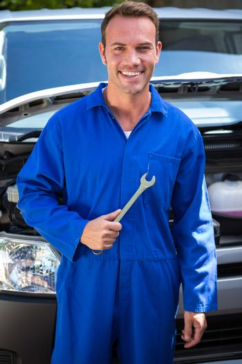 Mechanic holding spanner at the garage