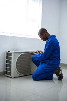 Handyman testing air conditioner