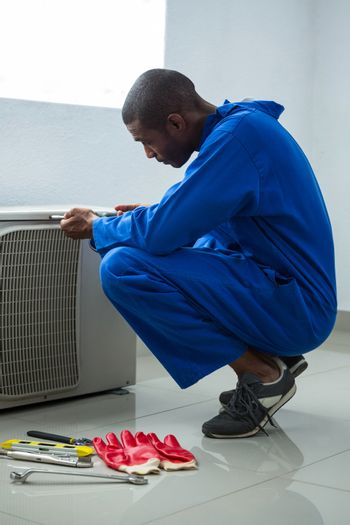 Handyman testing air conditioner with screwdrive