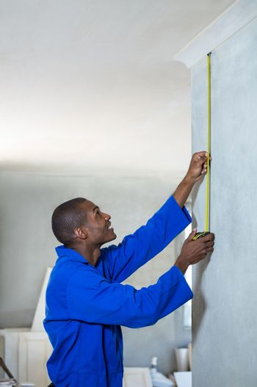 Handyman measuring a wall