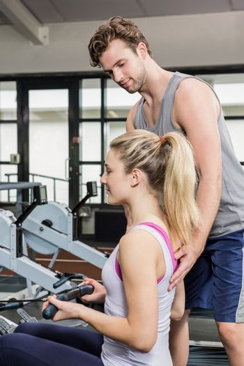 Trainer assisting a woman on rowing machine