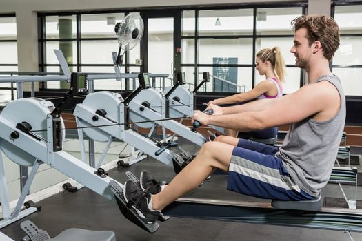 Man and woman working out on rowing machine