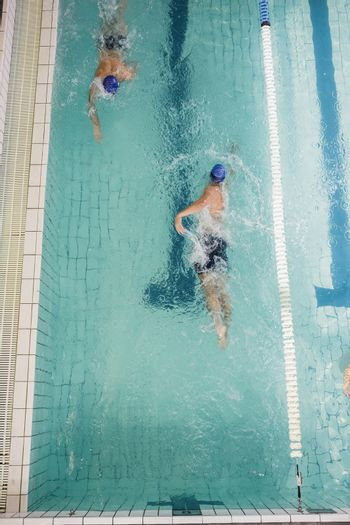 Swimmers doing the freestyle stroke in swimming pool