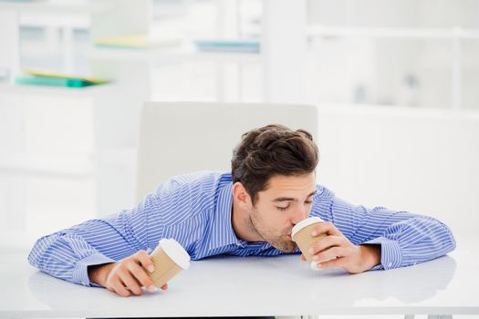 Businessman having coffee from disposable cup