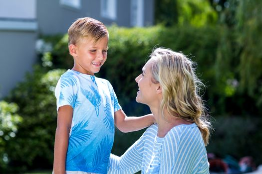 Smiling mother with son at backyard