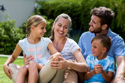Happy family enjoying while sitting on grass in yard