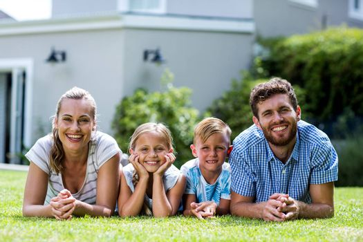 Front view of happy family lying on grass in yard