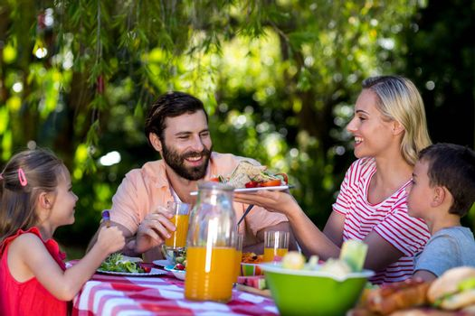 Mother offering salad while family sitting at table in yard