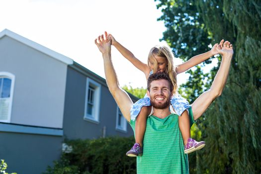 Portrait of father carry daughter on shoulders in yard