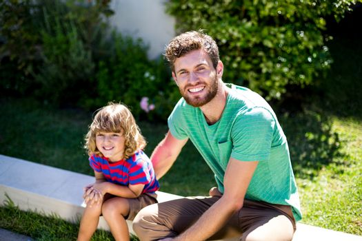 Father with son sitting in backyard
