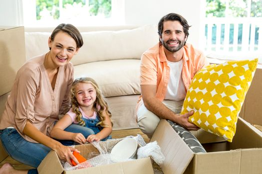 Portrait of happy family unpacking boxes in new house