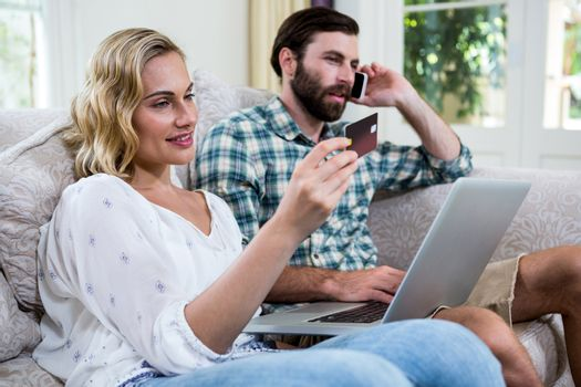 Woman holding debit card by man talking on phone with laptop