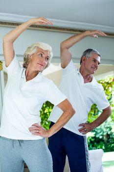 Senior couple bending while doing aerobics