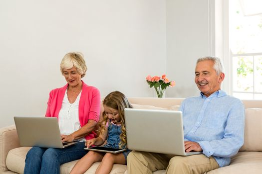 Happy grandparents and girl using technology while sitting on sofa