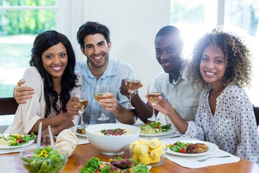 Two couples holding wine glass while having meal at home