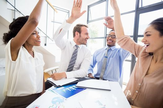 Happy businesspeople raising their hands during a meeting